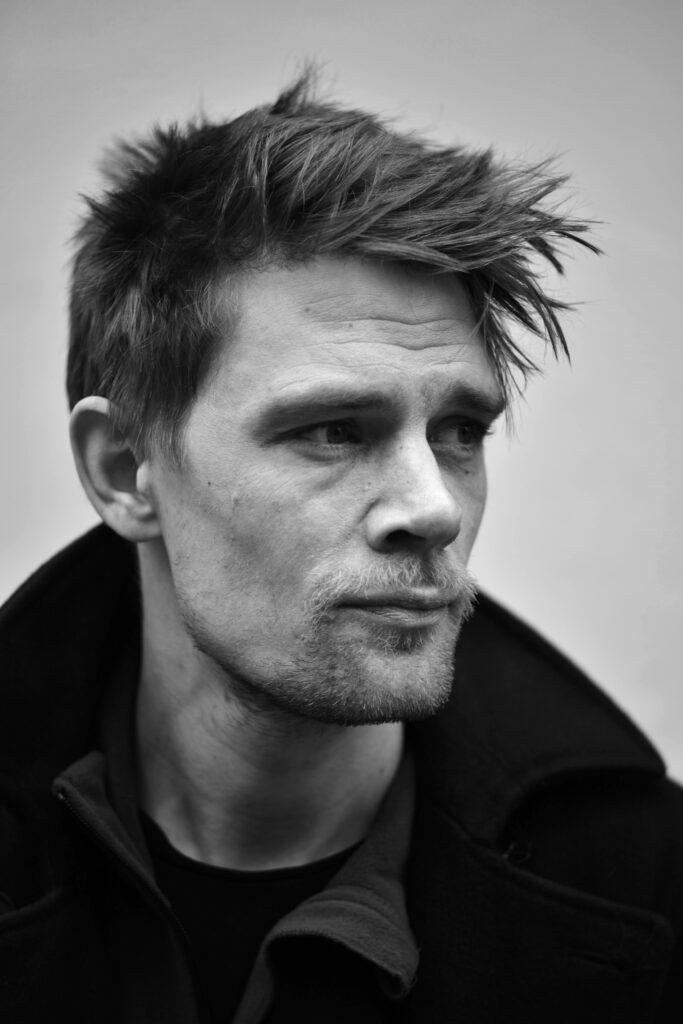 Simon Fensholm konstnär, porträtt i svartvitt. Fotograf Janus Engel Rasmussen.